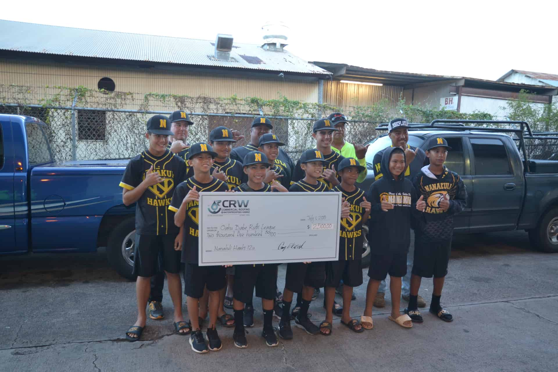Nanakuli Hawks holding check at CRW warehouse.